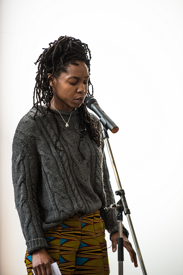 Natacha Omikemi Bryan, eyes shut, standing at microphone