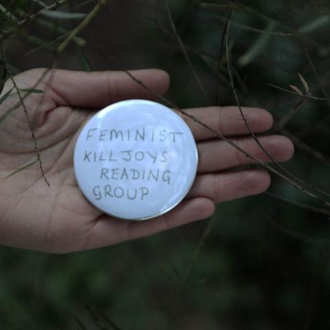 hand holds badge with words 'feminist killjoys reading group' against greenery